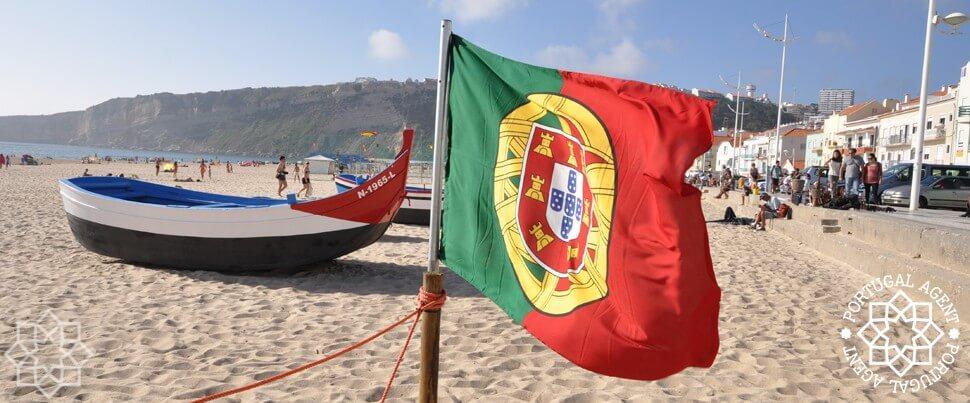 Portugals flagga på stranden vid Marginalen i Nazaré